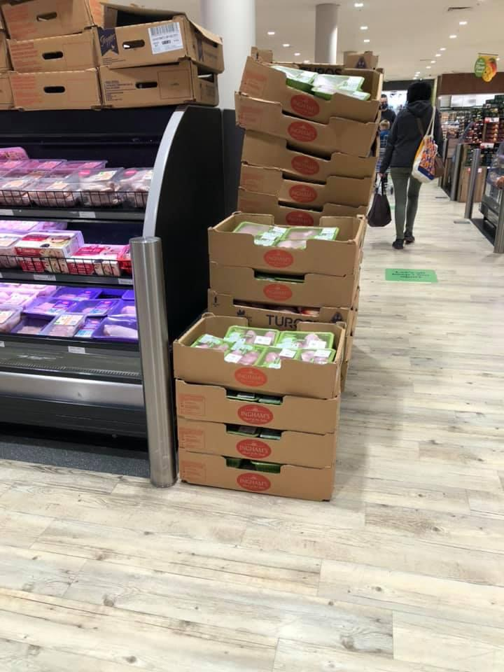 Pictured are 27 boxes of raw chicken stacked next to the fridge inside a Melbourne Woolworths.