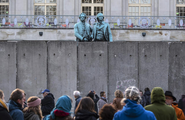 A wall, an art performance of the National Theatre Weimar, stands in front of the memorial of German poets Johann Wolfgang von Goethe, left, and Friedrich Schiller, right, prior to the 30th anniversary of the fall of the Berlin wall in October 2019. (AP Photo/Jens Meyer)