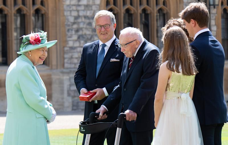 WINDSOR, ENGLAND - JULY 17: Queen Elizabeth II talks with Captain Sir Thomas Moore and his family after presenting him with the insignia of Knight Bachelor during an investiture ceremony at Windsor Castle on July 17, 2020 in Windsor, England. British World War II veteran Captain Tom Moore raised over £32 million for the NHS during the coronavirus pandemic. (Photo by Pool/Samir Hussein/WireImage)