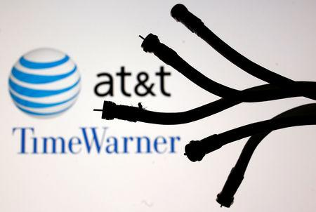 Coaxial TV Cables are seen in front of AT&T and Time Warner logos in this picture illustration