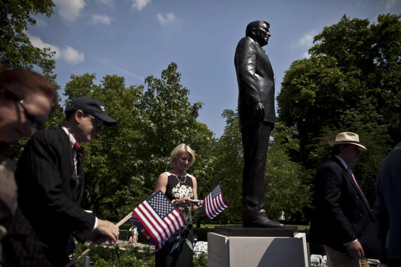 People take their turn to pose for photographs beside a statue of the late U.S. President Ronald Reagan after its unveiling outside the U.S. embassy in London, Monday, July 4, 2011.  The 10 foot bronze was unveiled Monday to mark the centenary of Reagan's birth.  (AP Photo/Matt Dunham)