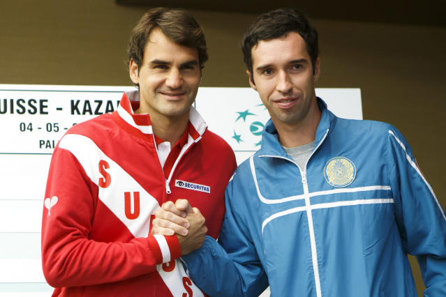 Roger Federer, left, of Switzerland, poses with Mikhail Kukushkin, right, of Kazakhstan, after the draw prior to the Davis Cup World Group quarterfinals between Switzerland and Kazakhstan, in Geneva, Switzerland, Wednesday, April 2, 2014. (AP Photo/Keystone, Salvatore Di Nolfi)