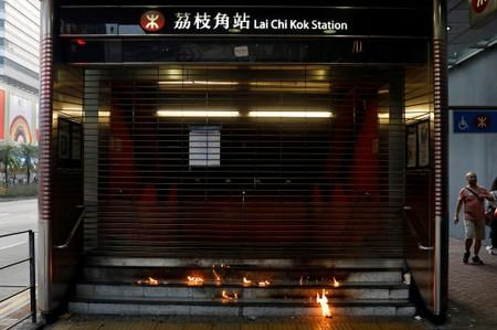 Petrol bombs burn at the entrance to the MTR station after a protest against the invocation of the emergency laws in Hong Kong