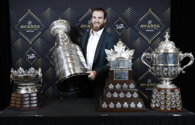 FILE - In this June 19, 2019, file photo, St. Louis Blues' Ryan O'Reilly poses with, from left, the Frank J. Selke Trophy, for top defensive forward; the Stanley Cup; the Conn Smythe Trophy, for MVP during the playoffs; and the Clarence S. Campbell Bowl, for the Western Conference playoff champions, at the NHL Awards in Las Vegas. Ryan OReilly stockpiled quite the hardware to show off at his Stanley Cup day. On display next to the Cup he helped the St. Louis Blues win were the Conn Smythe Trophy as playoff MVP and the Selke Trophy as the NHLs best defensive forward. Any player would gladly celebrate with those shiny centerpieces, though OReilly at 28 and on his third team is only now showing hes this kind of elite player.(AP Photo/John Locher, File)