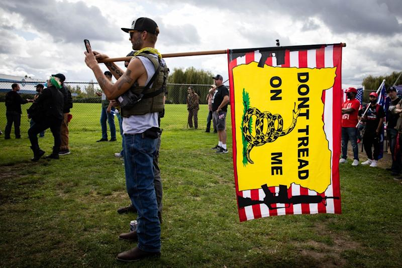 """A man holds a """"Don't tread on me"""" flag in the shape of Oregon with images of assault rifles on either side"""