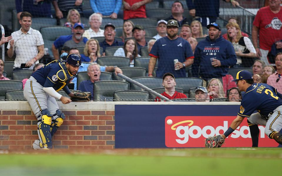 Oct 12, 2021; Cumberland, Georgia, USA; Milwaukee Brewers third baseman Luis Urias (2) catches a ball in foul territory that was deflected by catcher Omar Narvaez (10) during the fourth inning against the Atlanta Braves during game four of the 2021 ALDS at Truist Park. Mandatory Credit: Brett Davis-USA TODAY Sports
