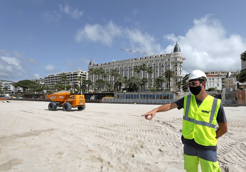 A worker wearing a protective face mask gestures on the beach of the Carlton hotel in Cannes