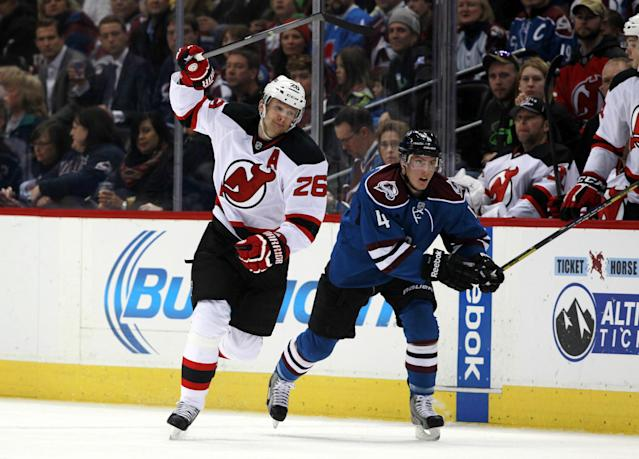 New Jersey Devils left wing Patrik Elias, left, of the Czech Republic, pursuea the puck with Colorado Avalanche defenseman Tyson Barrie in the first period of an NHL hockey game in Denver, Thursday, Jan. 16, 2014. (AP Photo/David Zalubowski)