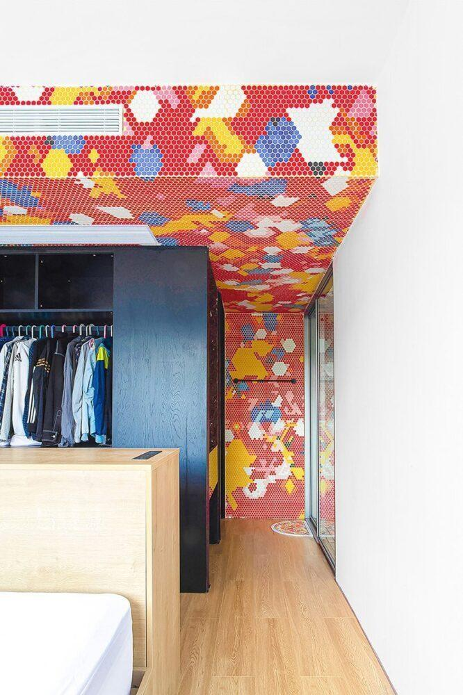 The bedroom walls inside the Live and Fun apartment are similarly adorned in primary colored tile mosaics.