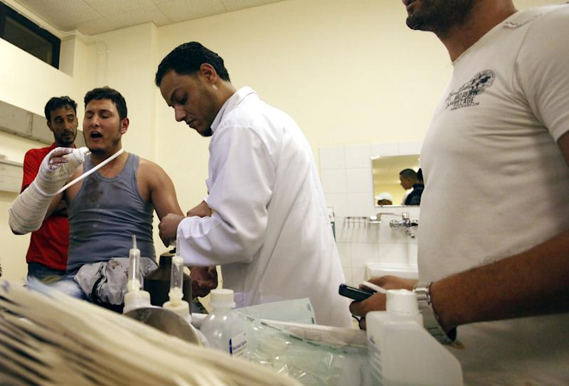 A Libyan Doctor at Benghazi Medical Center, helps a Libyan civilian who was shot in his arm during a raid on armed Islamic militias compounds in Benghazi, Libya, Saturday, Sept. 22, 2012. Hundreds of protesters stormed the compound of one of Libya's strongest armed Islamic extremist groups Friday, evicting militiamen and setting fire to their building as the attack that killed the U.S. ambassador and three other Americans sparked a public backlash against armed groups that run rampant in the country and defy the country's new, post-Moammar Gadhafi leadership. (AP Photo/Mohammad Hannon)
