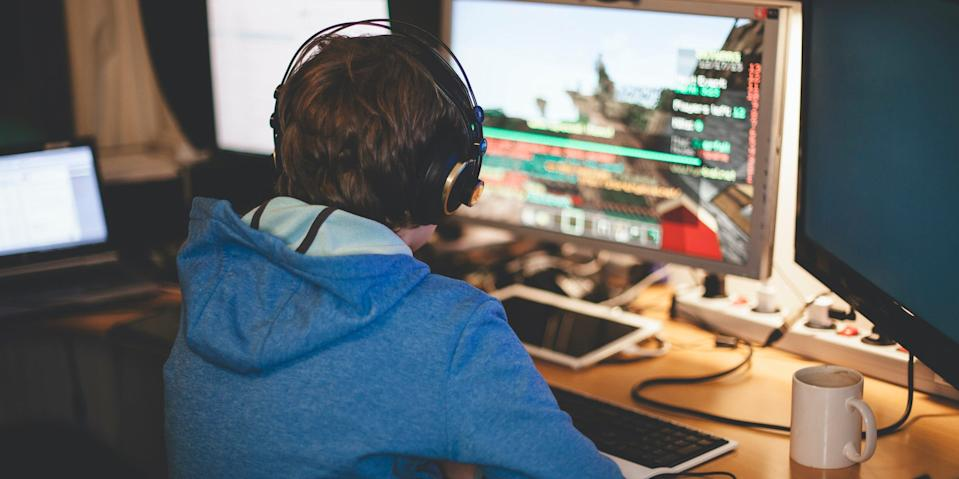 boy gaming video games on computer headphones