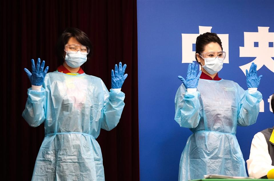 EVA Air (left) and China Airlines (right) flight attendants pose at press conference donning their new protective gear. (Courtesy of the CECC)