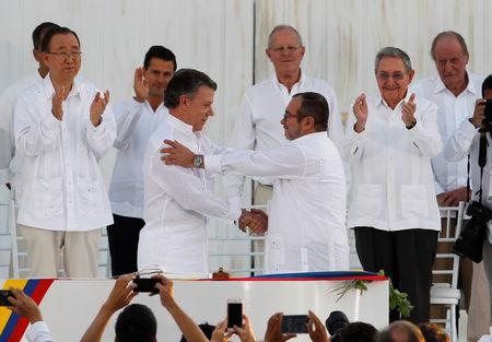 Colombian President Juan Manuel Santos (L) and Marxist rebel leader Timochenko shake hands after signing an accord ending a half-century war that killed a quarter of a million people, in Cartagena