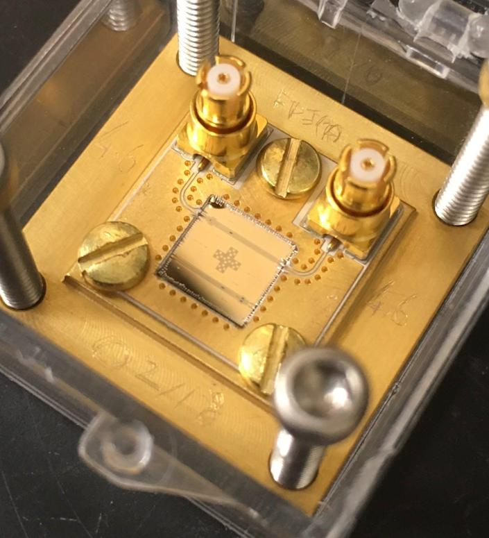 A superconducting circuit, a small gold-colored square mounted onto a golden metal board.