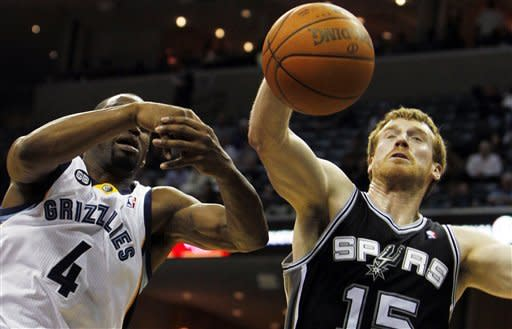 San Antonio Spurs guard Matt Bonner (15) stretches for a rebound under pressure by Memphis Grizzlies guard Sam Young (4) in the second half of an NBA basketball game on Monday, Jan. 30, 2012, in Memphis, Tenn. The Spurs won 83-73. (AP Photo/Jim Weber)