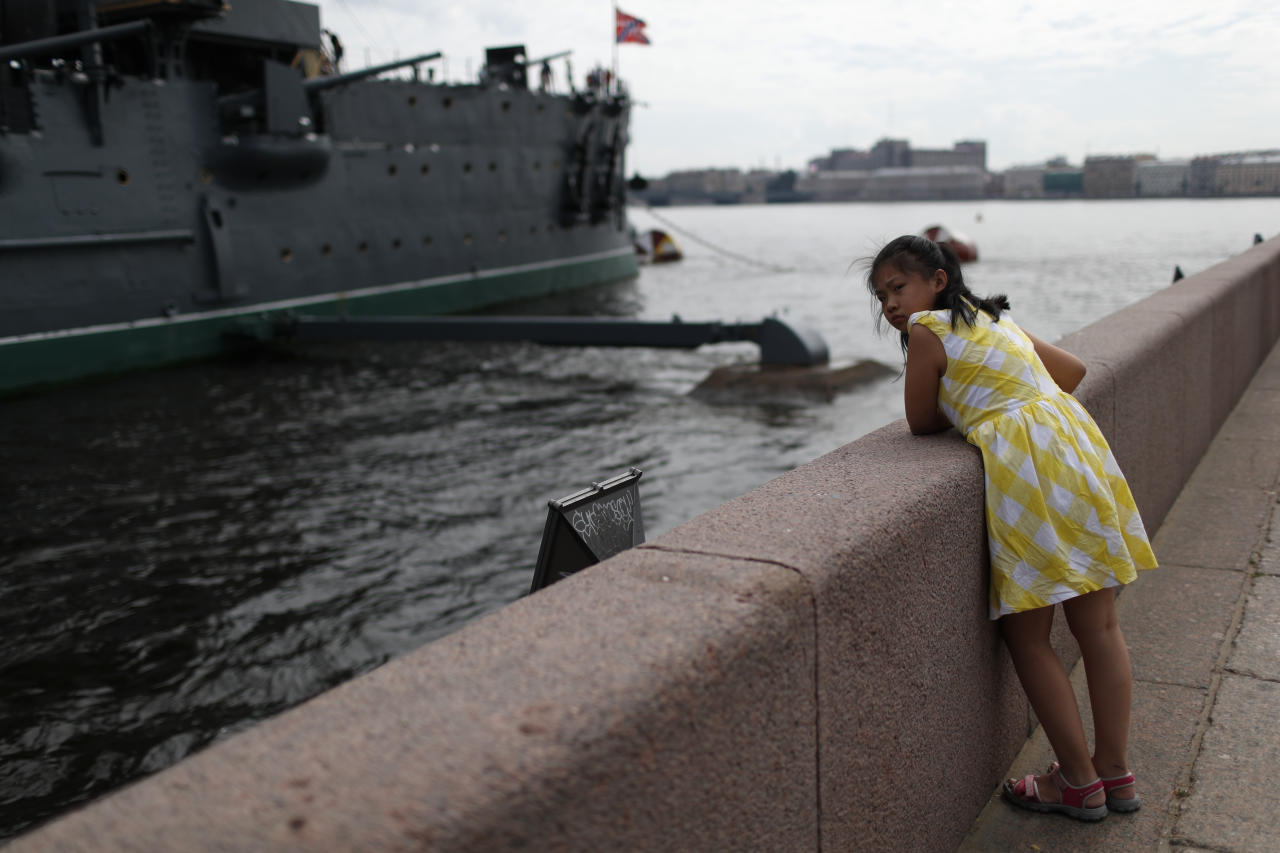 A young girl watches the Aurora cruise ship docked at the Neva river during the 2018 soccer World Cup in St. Petersburg, Russia, Friday, July 13, 2018. (AP Photo/Natacha Pisarenko)