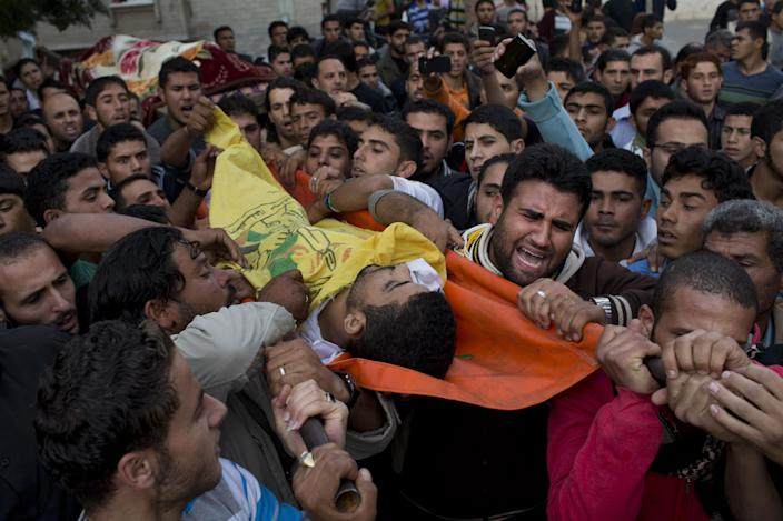 Palestinians carry the body of Mohammed Salman during his funeral in Beit Lahia, north Gaza, Friday, Nov. 16, 2012. According to relatives, Tahrer Salman and Mohammed Salman and were killed after an Israeli airstrike hit the yard of their house. (AP Photo/Bernat Armangue)