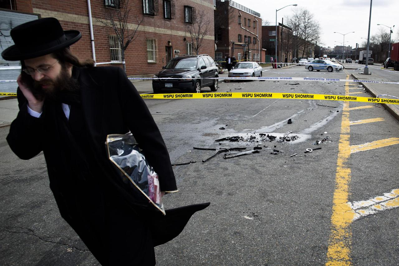 A man walks past debris from a fatal accident that claimed the lives of two expectant parents on their way to the hospital early, Sunday, March 3, 2013, in the Brooklyn borough of New York. A driver struck the car the couple were riding in early Sunday morning, killing both parents while their baby, whowas born prematurely, survivedand isin critical condition. (AP Photo/John Minchillo)