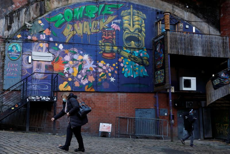 A woman in a face mask walks past the closed Zombie Shack nightclub in Manchester