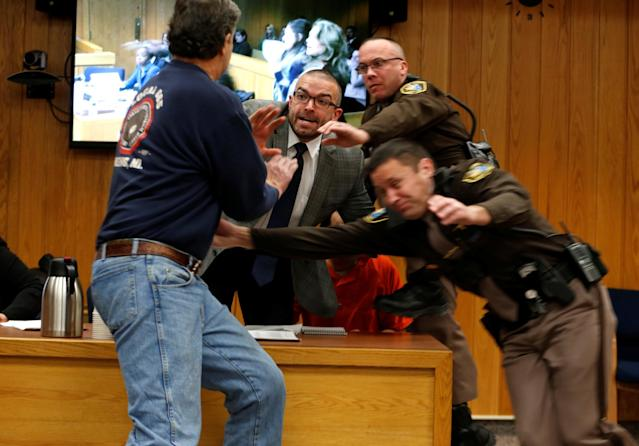 Randall Margraves (L) lunges at disgraced former USA Gymnastics team doctor Larry Nassar (wearing orange) during victim impact statements in a Michigan courtroom. (Reuters)