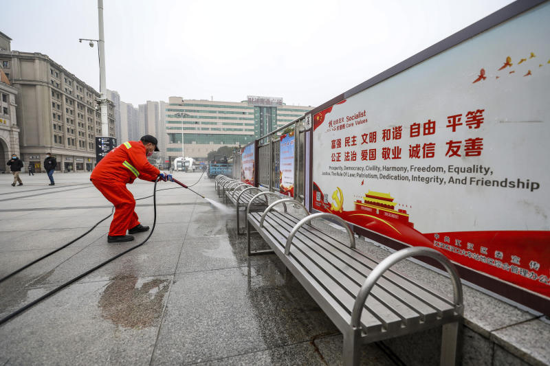 A worker hoses down benches outside the closed Hankou Railway Station in Wuhan in central China's Hubei Province, Thursday, Jan. 23, 2020. China closed off a city of more than 11 million people Thursday in an unprecedented effort to try to contain a deadly new viral illness that has sickened hundreds and spread to other cities and countries amid the Lunar New Year travel rush. (Chinatopix via AP)