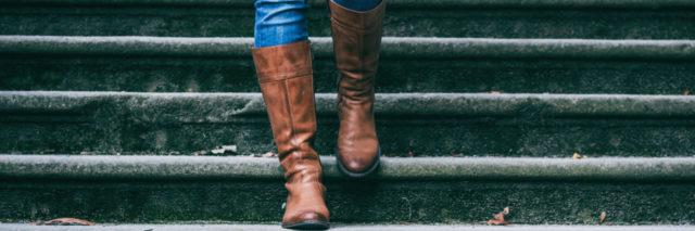 woman walking down the stairs wearing boots