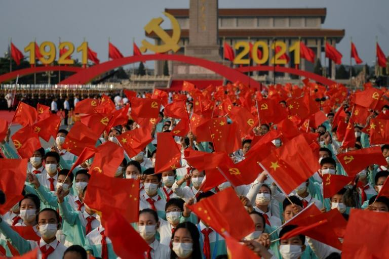 In China's immense Tiananmen Square, tens of thousands of handpicked spectators cheered, sang, and waved flags