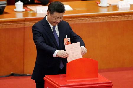 FILE PHOTO: Chinese President Xi Jinping drops his ballot during a vote on a constitutional amendment lifting presidential term limits, at the third plenary session of the National People's Congress (NPC) at the Great Hall of the People in Beijing, China March 11, 2018. REUTERS/Jason Lee/File Photo