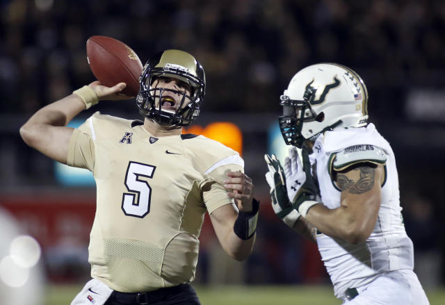Central Florida quarterback Blake Bortles (5) is pressured by South Florida defensive lineman Aaron Lynch (19) during the first half of an NCAA college football game on Friday, Nov. 29, 2013, in Orlando, Fla. (AP Photo/Reinhold Matay