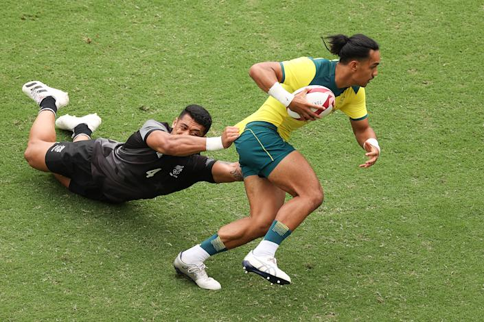 <p>Dietrich Peter Roache of Team Australia is tackled by Etene Nanai-Seturo of Team New Zealand during the Men's Pool A Rugby Sevens match between New Zealand and Australia on day four of the Tokyo 2020 Olympic Games at Tokyo Stadium on July 27, 2021 in Chofu, Tokyo, Japan. (Photo by Dan Mullan/Getty Images)</p>