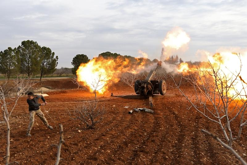 An opposition fighter fires a cannon from a village near Al-Tabanah during ongoing battles with government forces in Syria's Idlib province on January 11, 2018