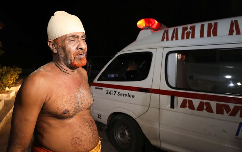 An injured civilian stands outside Madina Hospital after a blast at the Luul Yemeni restaurant near the port in Mogadishu