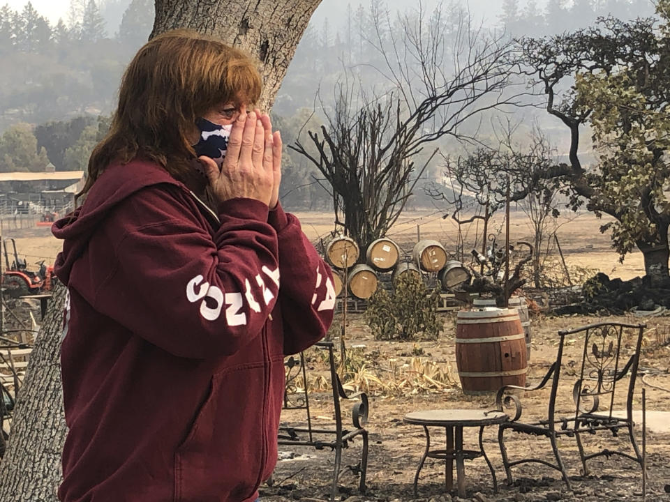 """Nikki Conant cries as she looks at the debris of her home and business, """"Conants Wine Barrel Creations,"""" after the Glass/Shady fire completely engulfed it, Wednesday, Sept. 30, 2020, in Santa Rosa, Calif. The Conants escaped with their lives, which we are grateful for, but they barely made it out with the clothes on their backs in the wake of the fire. The Glass and Zogg fires are among nearly 30 wildfires burning in California. (AP Photo/Haven Daley)"""