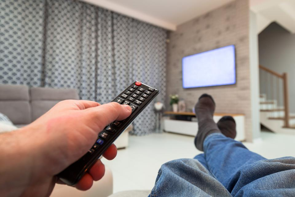 Man watching TV in living room with remote in the hand.