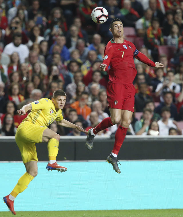 Portugal's Cristiano Ronaldo, right, challenges for the ball with Ukraine's Vitaliy Mykolenko during the Euro 2020 group B qualifying soccer match between Portugal and Ukraine at the Luz stadium in Lisbon, Friday, March 22, 2019. (AP Photo/Armando Franca)