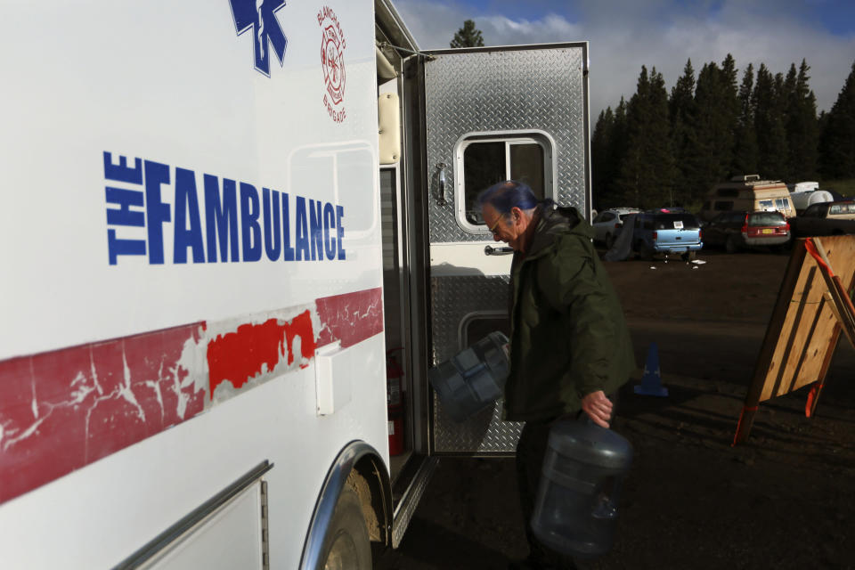 """Oregon EMT Thomas Curotto carries empty water jugs to his """"fambulance"""" in the parking lot of the Rainbow Gathering on Friday, July 2, 2021, in the Carson National Forest, outside of Taos, N.M. More than 2,000 people have made the trek into the mountains of northern New Mexico as part of an annual counterculture gathering of the so-called Rainbow Family. While past congregations on national forest lands elsewhere have drawn as many as 20,000 people, this year's festival appears to be more reserved. Members. (AP Photo/Cedar Attanasio)"""