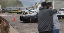 Family and friends of the victims who died in a shooting, comfort each down the street from the scene in Colorado Springs, Colo., on Sunday, May 9, 2021. The suspected shooter was the boyfriend of a female victim at the party attended by friends, family and children. He walked inside and opened fire before shooting himself, police said. Children at the attack weren't hurt and were placed with relatives.(Jerilee Bennett/The Gazette via AP)