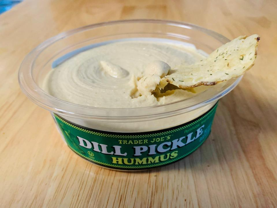 A chip in an open container of Trader Joe's dill-pickle hummus on a light wood table