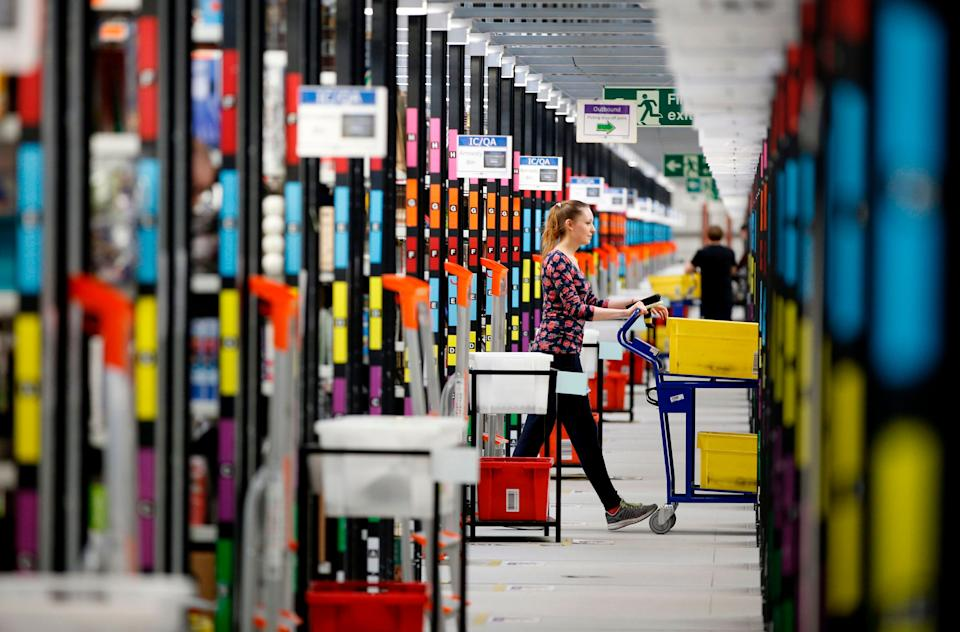 A 'picker' worker collects items from storage shelves as she collates a customer order inside an Amazon.co.uk fulfillment centre in Hemel Hempstead, north of London, in 2015 (Photo: ADRIAN DENNIS via Getty Images)