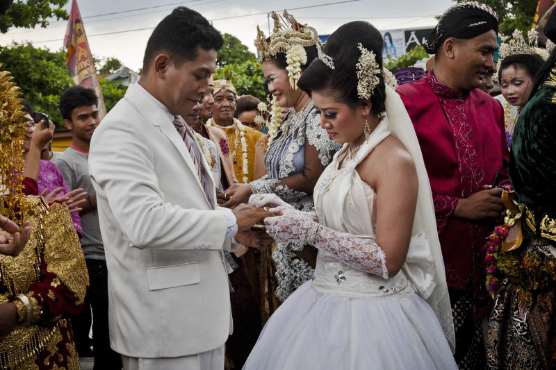 Brides and grooms exchange rings during a mass wedding ceremony on December 12, 2012 in Yogyakarta, Indonesia. Twelve couples participated in a mass wedding as today saw a surge in marriage across the globe to mark the once in a century date of 12/12/12.  (Photo by Ulet Ifansasti/Getty Images)