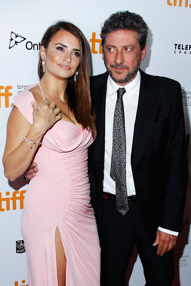 "While Penelope Cruz is distracted with adjusting her dress at the premiere of ""Twice Born,"" director Sergio Castellitto casts a sideways glance that shows he knows just how lucky he is."