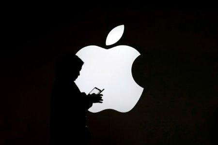 A woman looks at the screen of her mobile phone in front of an Apple logo outside its store in Shanghai, China July 30, 2017. REUTERS/Aly Song