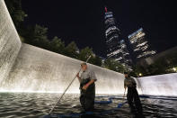 """James Maroon, left, cleans the bottom of the south pool of the 9/11 Memorial with a vacuum, Wednesday, Aug. 4, 2021, in New York. On Sept. 11, 2001 he was going to work at the New York Mercantile Exchange, just west of the twin towers. """"I was getting ready to cross the Westside Highway when the first plane hit and people were running up behind me,"""" he said. """"I thought a truck or something hit the walkway. I got out, looked up and the first plane was in the building. I thought it was just a small commuter plane because you didn't see a plane, just a hole. I ended going into work and then the second plane hit. I couldn't figure out where to go. Pretty much everything was closed off. I hooked up with a guy I worked with and we started walking up the Westside Highway and I looked back and the tower collapsed. Unbelievable."""" (AP Photo/Mark Lennihan)"""