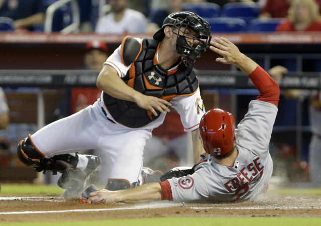 St. Louis Cardinals' David Freese, right, slides safely into home plate as Miami Marlins catcher Rob Brantly attempts the tag during the first inning of a baseball game on Saturday, June 15, 2013, in Miami. (AP Photo/Wilfredo Lee)