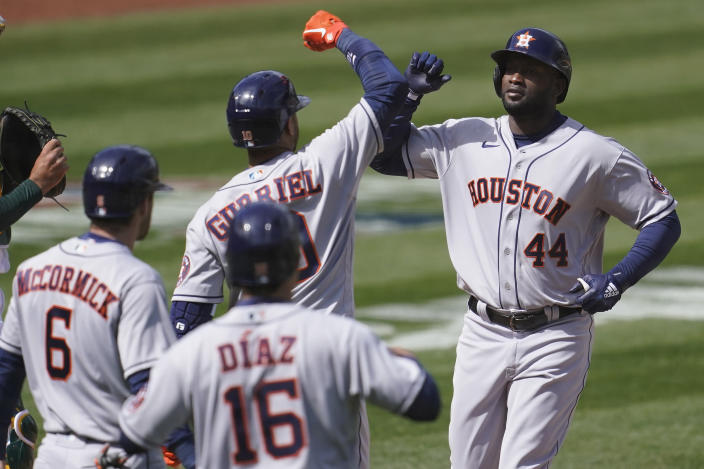 CORRECTS TO ALSO SCORED ALEDMYS DIAZ (16) NOT YULI GURRIEL - Houston Astros' Yordan Alvarez (44) celebrates with Yuli Gurriel, center, after hitting a three-run home run that also scored Chas McCormick (6) and Aledmys Diaz (16) during the fifth inning of a baseball game against the Oakland Athletics in Oakland, Calif., Saturday, April 3, 2021. (AP Photo/Jeff Chiu)