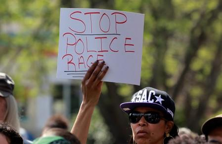 FILE PHOTO: A demonstrator holds a sign at a rally to protest the police shooting of Stephon Clark, in Sacramento