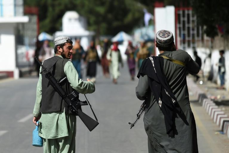 Taliban fighters walk at the main entrance gate of Kabul airport -- they are primed to take control of the facility when US forces leave (AFP/WAKIL KOHSAR)