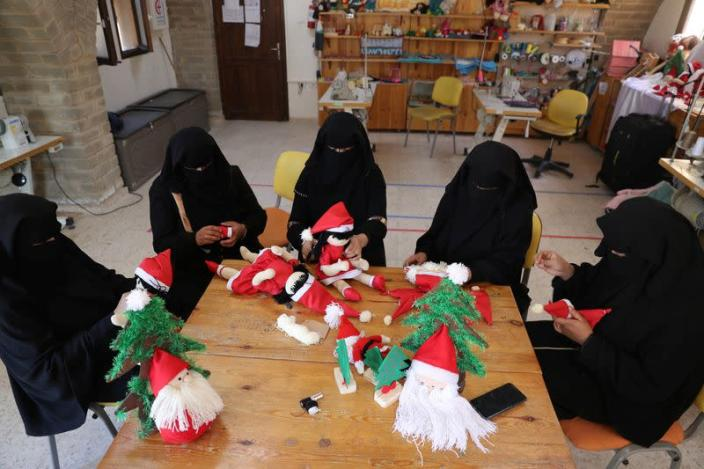Image: Palestinian women wearing face veil, niqab, make Santa-themed Christmas toys in the northern Gaza Strip