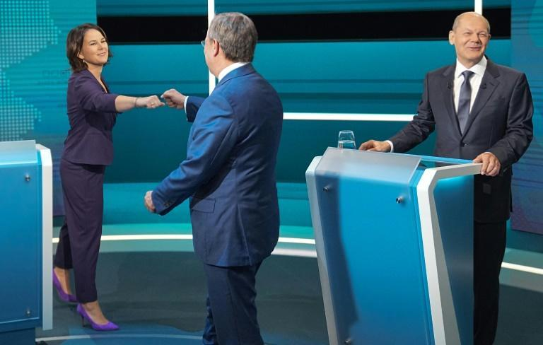 The candidates to become the next German Chancellor on the debate platform; Annalena Baerbock and Armin Laschet fist bump next to Olaf Scholz (AFP/Michael Kappeler)