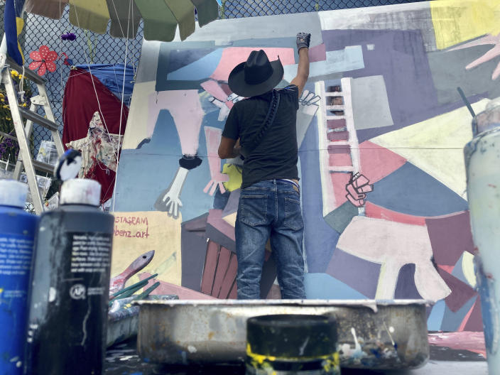 Roberto Marquez paints a mural, Friday, July 9, 2021 in Surfside, Fla. Roberto Marquez flew from Dallas to Miami nearly two weeks ago, hoping to add his hands to those digging through the rubble of a fallen South Florida condo building. But once there, the muralist was disappointed to hear that his help was appreciated but not needed. Still, the Dallas artist felt compelled to contribute to the cause, something that might uplift the Surfside community amid so much anguish. That's when he decided he would use his art to help translate pain into hope and resilience. (AP Photo/ Stacey Plaisance)